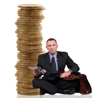 Man sitting near a stack of coins