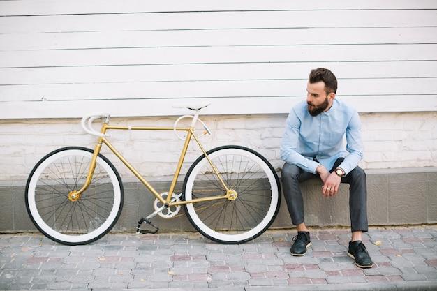 白い壁と自転車の近くに座っている男