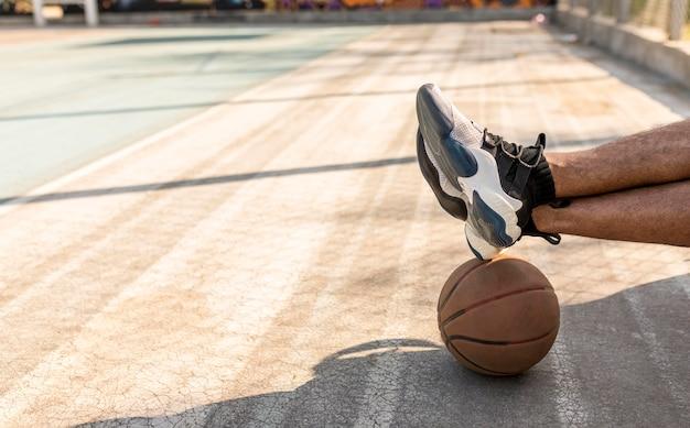 Человек сидит рядом с баскетбольным мячом