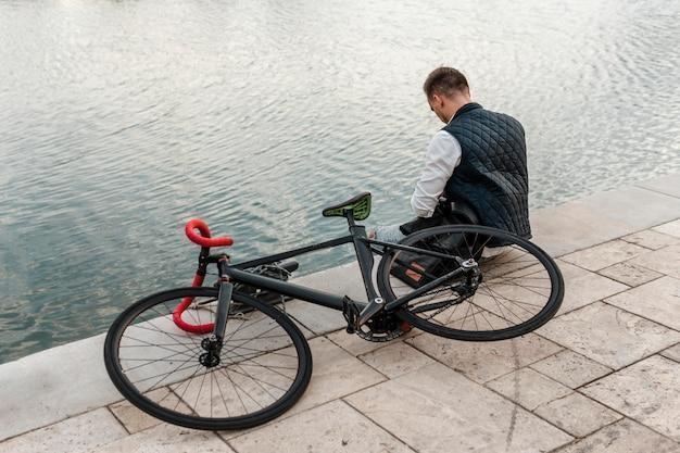 自転車で湖の隣に座っている男