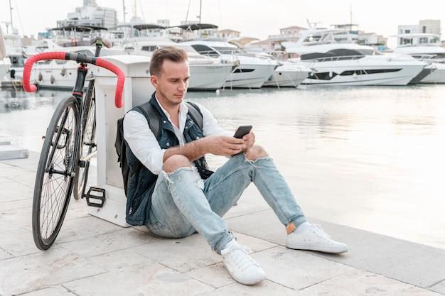 Человек сидит рядом со своим велосипедом и играет по телефону