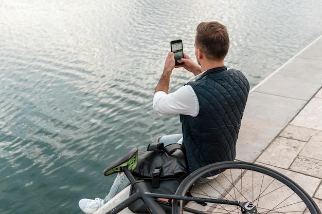 自転車の横に座って湖の写真を撮る男
