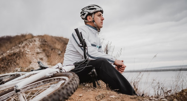 Человек сидит рядом со своим горным велосипедом