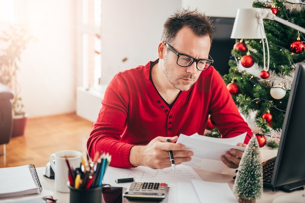 Man sitting at the office desk and reading letter Premium Photo
