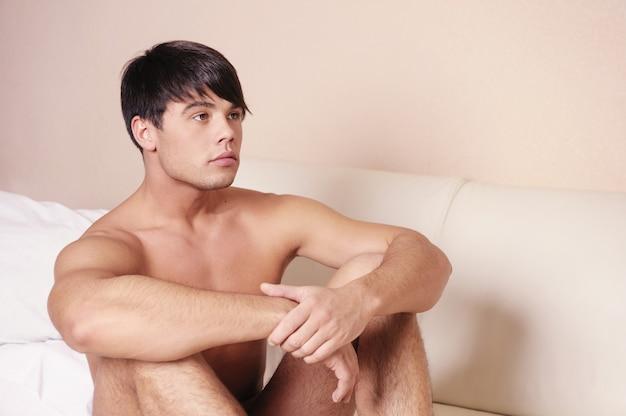 ベッドの上に座っている男。