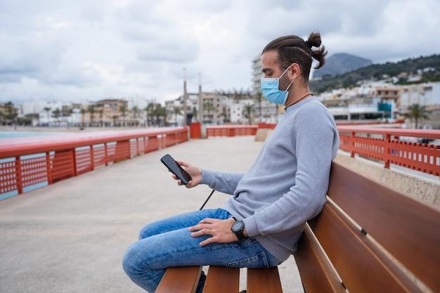 彼の携帯電話を見ているベンチに座っている男。
