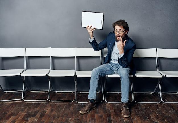 椅子に座っている男が就職の面接のキャリアを再開