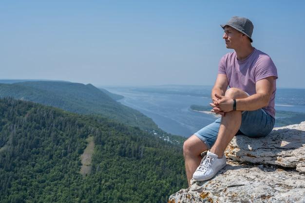 절벽 가장자리에 앉아 웃고 있는 남자가 주변의 아름답고 거친 지형을 바라보고 있습니다. 모험 여행 라이프 스타일. 개념 방랑벽. 활동적인 주말 휴가 야생의 자연 야외.