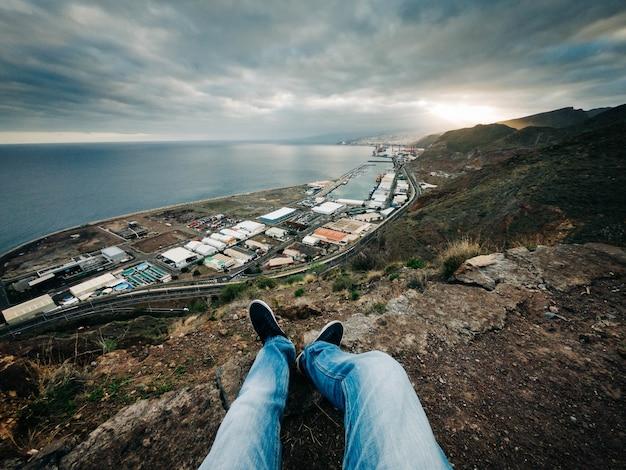 丘の上に座って景色を楽しむ男