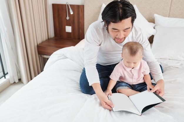 Мужчина сидит на кровати со своим маленьким сыном и читает ему интересную книгу, оставаясь дома из-за пандемии коронавируса