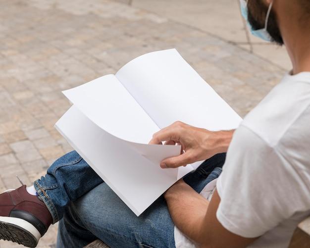 本を読んで屋外のベンチに座っている男