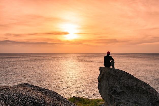 海に沈む夕日の観光で大きな岩に座っている男