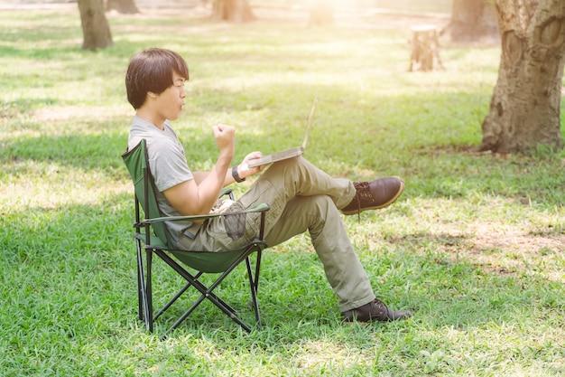 캠핑 의자에 앉아 정원에서 랩톱 컴퓨터를 사용하는 사람