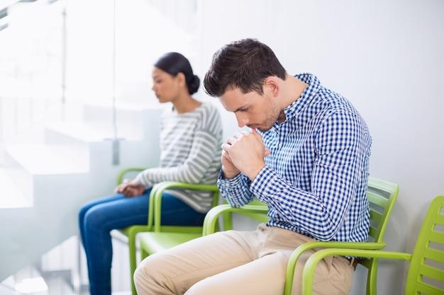 Человек сидит на стуле в больничном коридоре