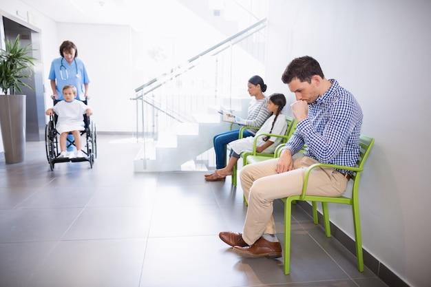 病院の廊下で椅子に座っている男
