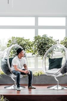 透明なアクリルの椅子に座っている男