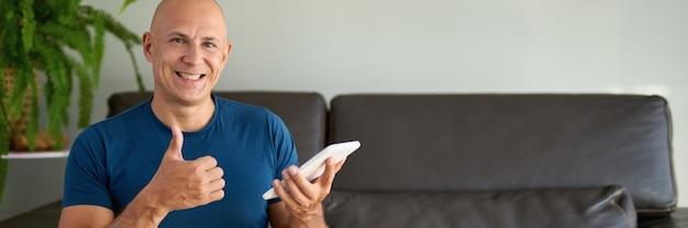 소파에 앉아 디지털 태블릿을 사용하는 사람. 집에서 태블릿을 통해 인터넷을 검색합니다.