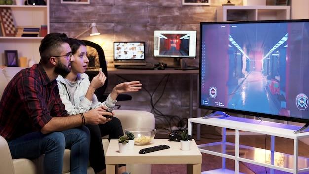 남자는 소파에 앉아 옆에 여자 친구와 함께 텔레비전에서 비디오 게임을 하고 있습니다.