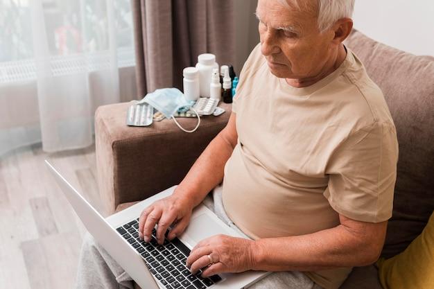 Человек сидит на диване с высоким углом ноутбука