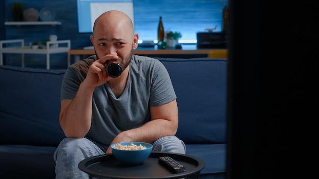 Человек сидит на уютном диване в гостиной в одиночестве, ест попкорн и пьет пиво