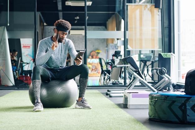 스마트 폰을 사용 하여 체육관 공에 앉아 남자