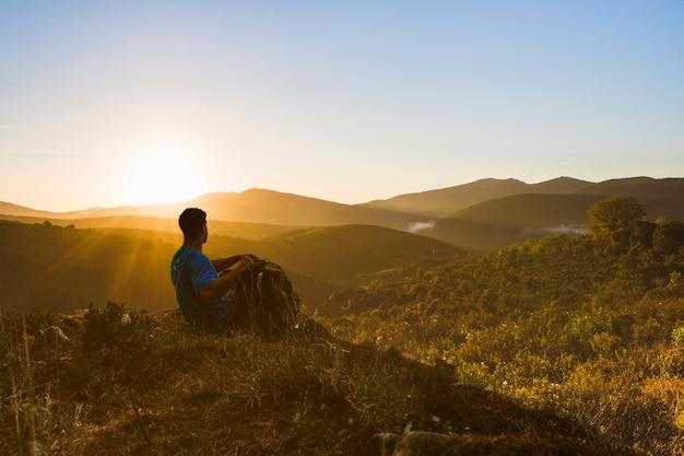 夕日の風景で丘の上に座っている男