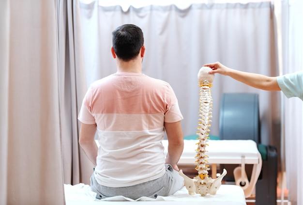 背を向けて病院のベッドに座っている男。彼の隣に背骨の模型を持っている医者。