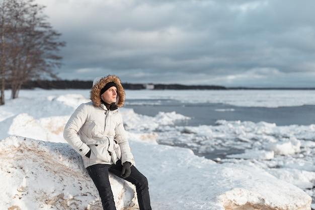 海沿いの氷のビーチに座っている男