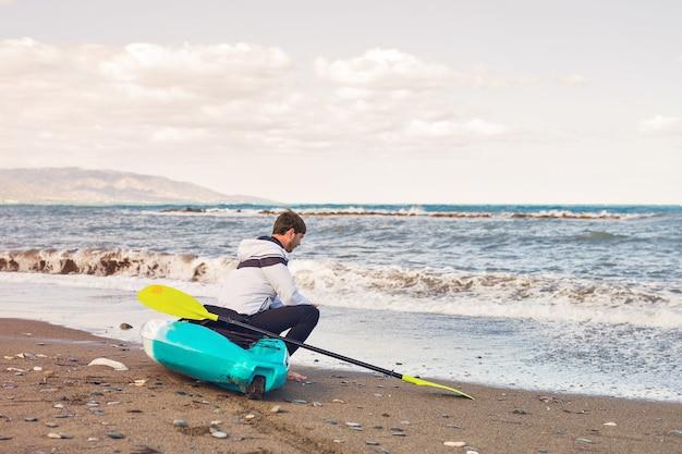 海のビーチでカヤックに座っている男