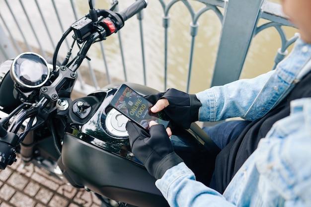バイクに座ってスマートフォンのアプリケーションを介して食品配達を注文する男性