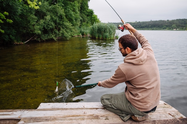 낚 싯 대와 물고기를 잡는 부두에 앉아 남자