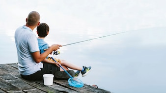 Man sitting on pier with his son fishing on lake