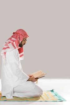祈りの敷物に座っている男