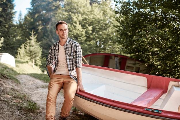 森の手漕ぎボートに座っている男