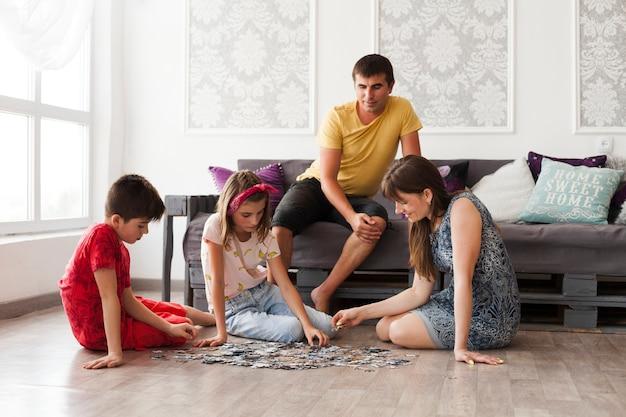 Человек сидит на диване и смотрит на свою жену и детей, играющих в головоломки дома