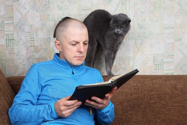 Человек сидит на диване и читает книгу библии