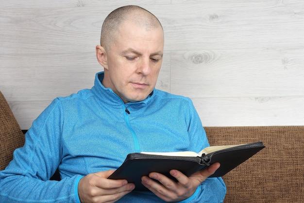 소파에 앉아 성경 책을 읽는 남자