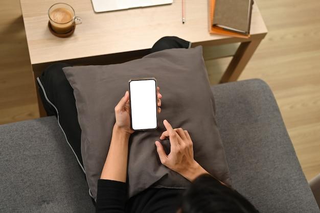 ソファに座ってスマートフォンでインターネットサーフィンをしている男性。