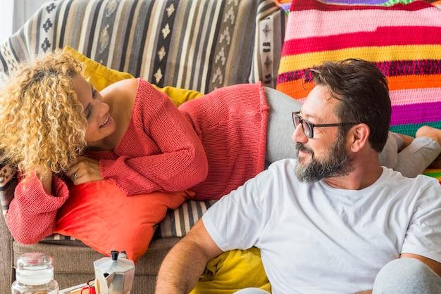 소파에 앉아서 집에서 소파에 누워 있는 아내와 이야기하는 남자. 사랑하는 부부는 집에서 함께 여가 시간을 보냅니다. 집에서 거실에서 휴식을 취하는 서로를 바라보는 백인 부부
