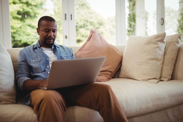 Человек сидит на диване и с помощью ноутбука в гостиной