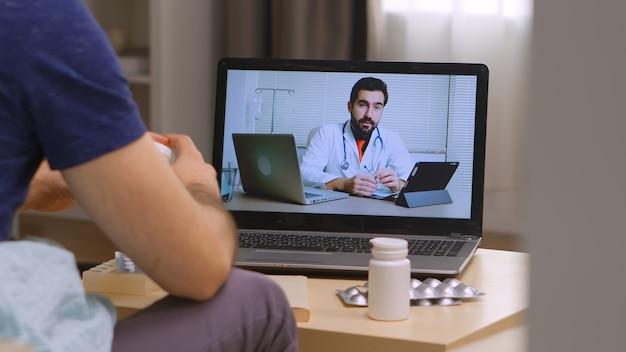 Covid 잠금 동안 온라인 의학 상담에 소파에 앉아 남자