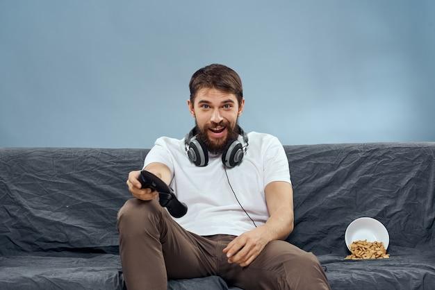 음식 레저 기술 라이프 스타일을 재생하는 게임 패드와 헤드폰을 착용하는 소파에 앉아 남자.