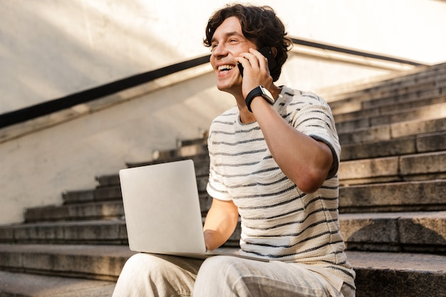 携帯電話で話しているラップトップコンピューターを使用して屋外の階段に座っている男。