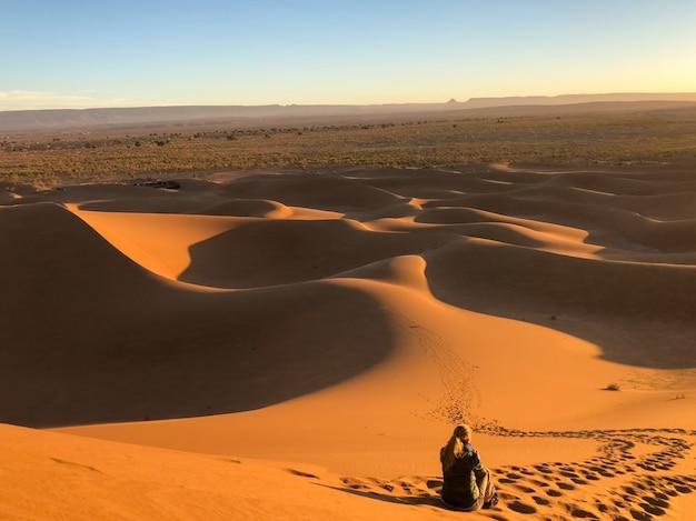 トラックに囲まれた砂漠の砂丘に座っている男