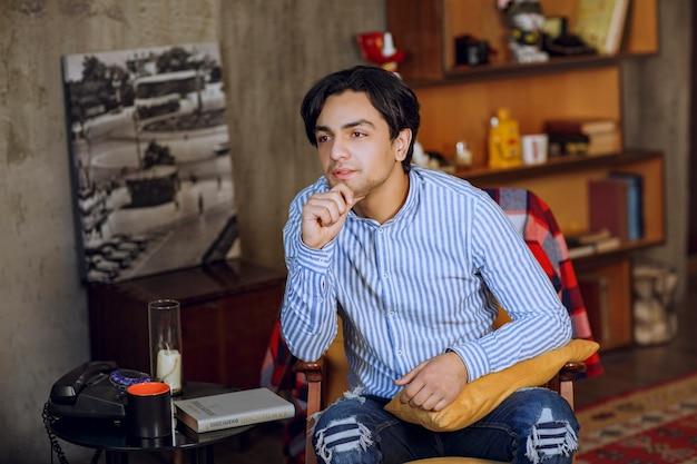 Человек сидит в кресле в кофейне и мечтает. фото высокого качества