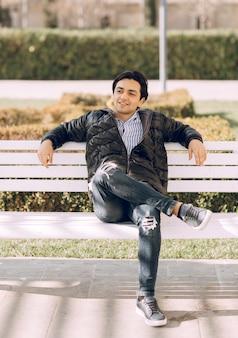 남자는 다른 다리에 한쪽 다리를 씌우고 벤치에 앉아. 고품질 사진