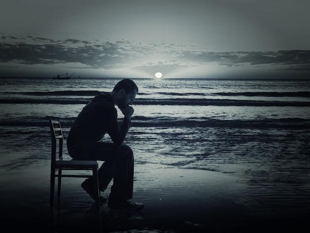 남자는 밤에 해 안에 의자에 앉아