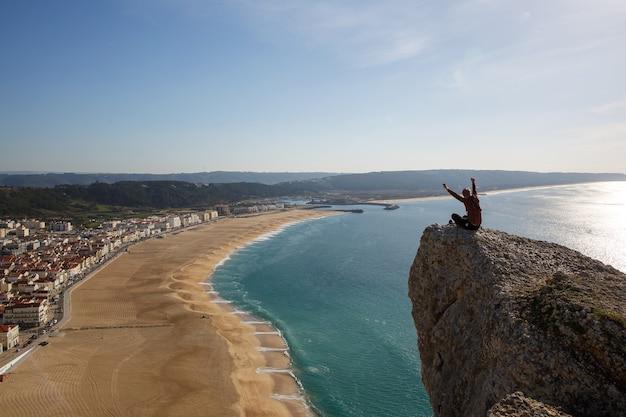 Человек сидит на скале, глядя сверху на морской пляж и небольшой город