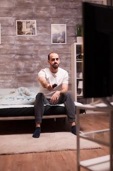 Человек сидит на краю своей кровати ночью, переключая каналы по телевизору с дистанционным управлением.
