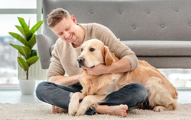 남자는 바닥에 앉아 골든 리트리버 강아지를 포옹. 집에서 햇볕이 잘 드는 방에서 강아지를 쓰다듬는 소유자